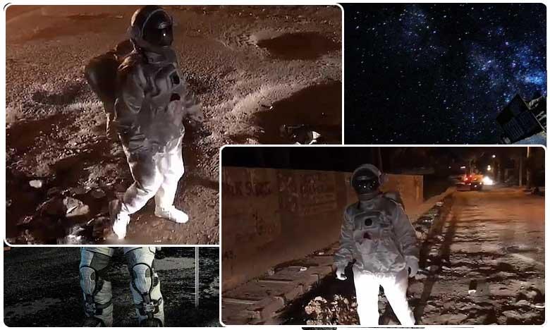 man dressed as an astronaut ' moonwalks ' over pot holes in benguluru road